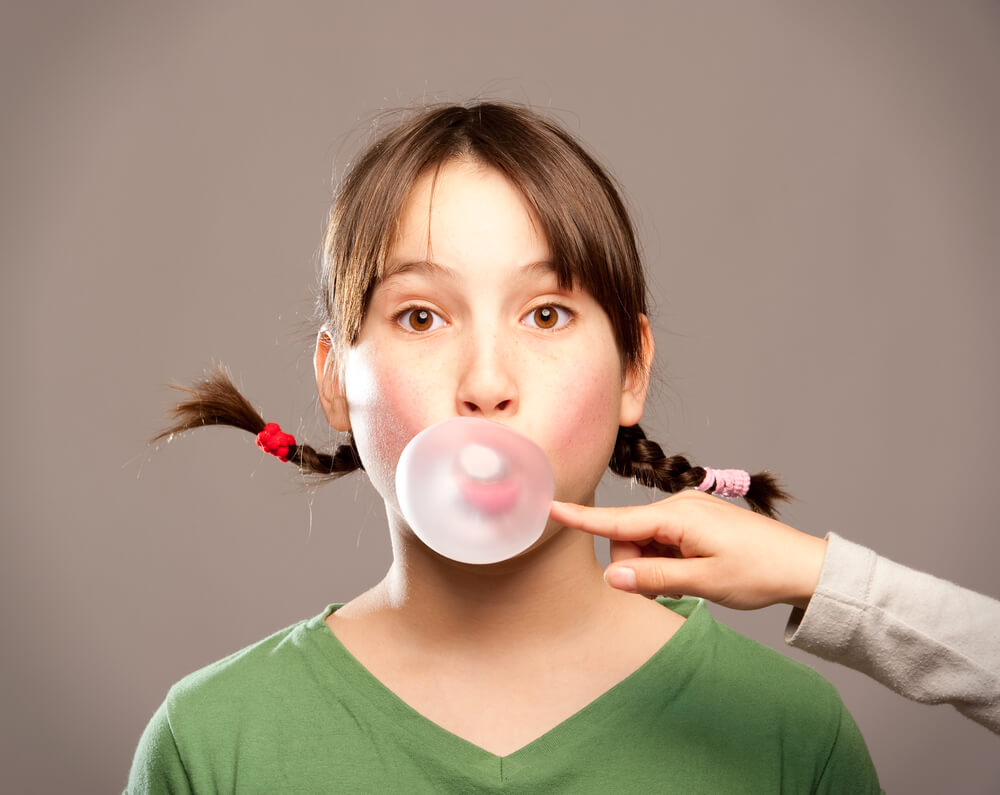 girl blowing gum bubble