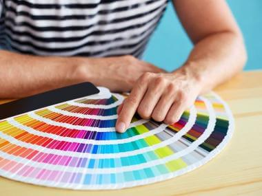 a hand choosing colors from color swatches