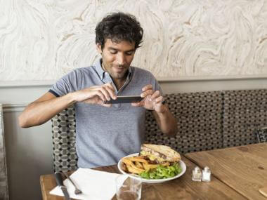 A man taking a picture of his food. Is he a gourmet or a gourmand?