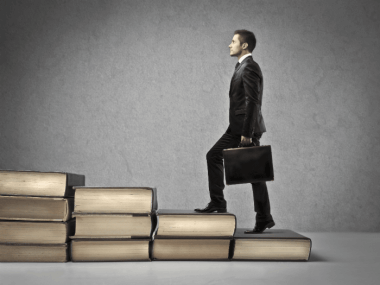 image of business man walking up stair books