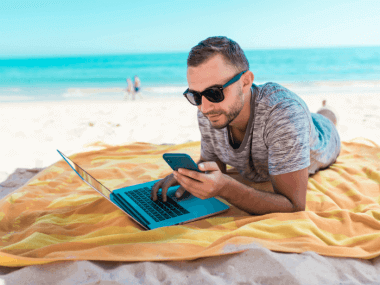 man using tech on the beach