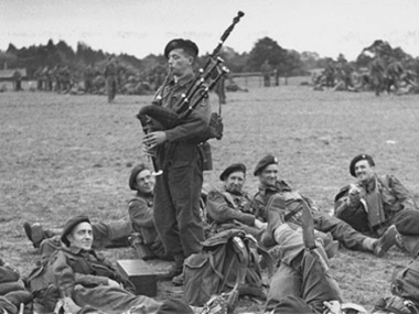 WWII soldiers and a bagpiper