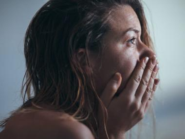 image of woman holding back tears