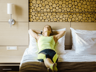 Photo of a woman laying in bed in workout clothes