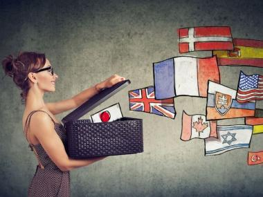A woman opening a box of flags as if she is setting languages free through translation