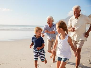 children running with their grandparents on the beach