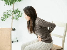 image of woman sitting on chair holding stomach