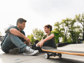 parent and child sitting at skatepark