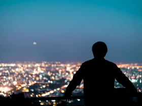 Man looking at city and night sky