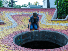 child peering down a deep hole
