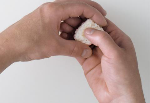 Lightly press, making a slight indentation in the top of the rice with your guide thumb and setting the length with the thumb and forefinger of your knife hand