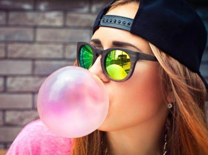 A woman blowing bubble gum and wearing a backward hat. She's informal!