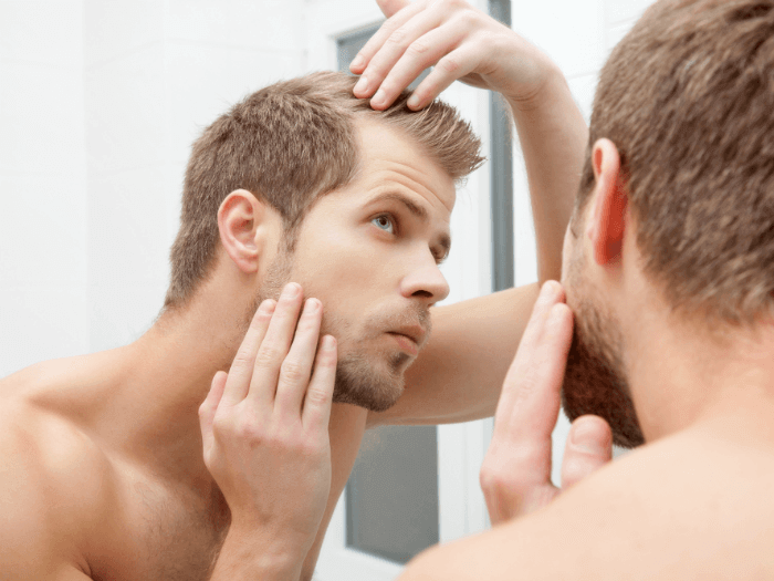 man examining his hair for any hair loss
