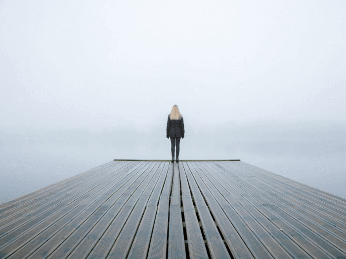 image of woman standing on edge of dock worried about climate change
