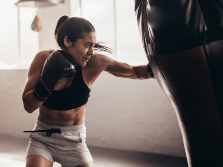 Photo of a woman hitting a heavy bag