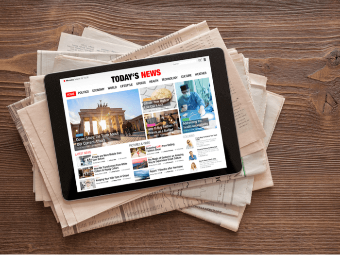 tablet on top of newspapers displaying daily news