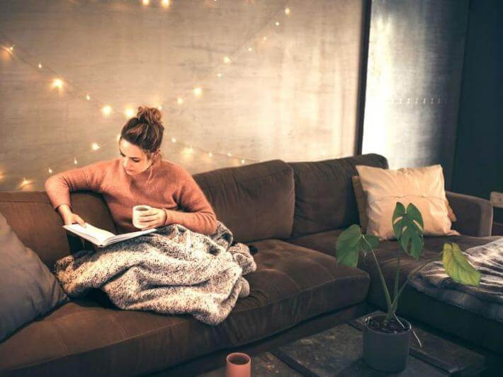 A woman hunkering down on her couch with a book