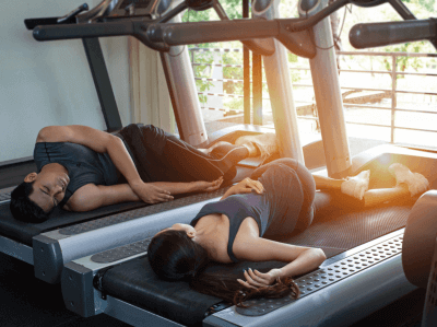 Photo of two people sleeping on a treadmill
