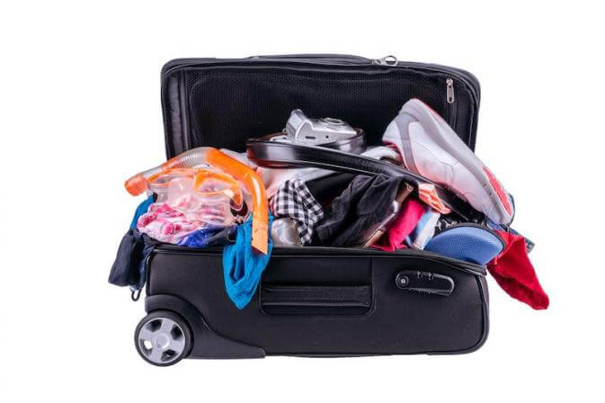 a dumped suitcase to illustrate unpacking lock, stock, and barrel at the airport